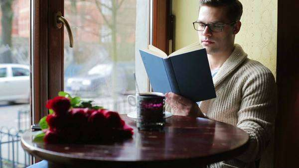 Man drinking coffee and reading book in the cafe Royalty-free stock video