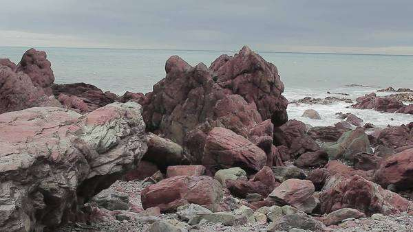 Wide shot of red rocks on a beach Royalty-free stock video