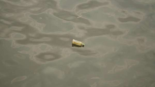 Handheld shot of a plastic bottle floating on water Royalty-free stock video