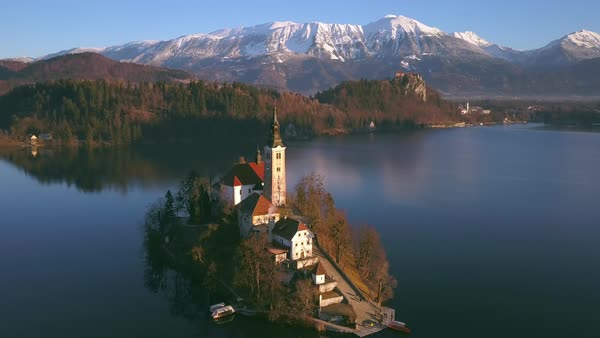 Bled Lake island aerial view flying around church at sunrise Royalty-free stock video
