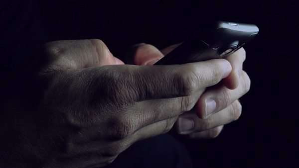 Male hands holding mobile device and playing video game on smart phone in dark room Royalty-free stock video