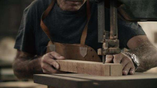 Handheld medium shot of a carpenter cutting a piece of wood in a workshop Royalty-free stock video