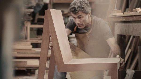 Handheld medium long shot of a carpenter in a workshop Royalty-free stock video