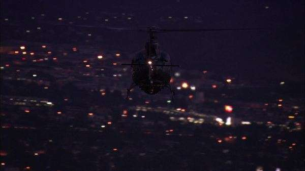 Handheld wide shot of a helicopter flying over a city at night Royalty-free stock video