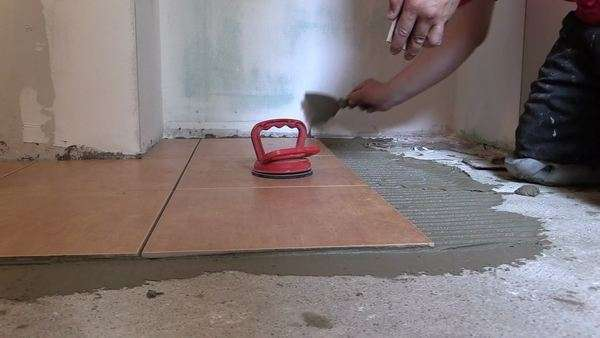 zoom in of man straighten tile on the cement surface with laser