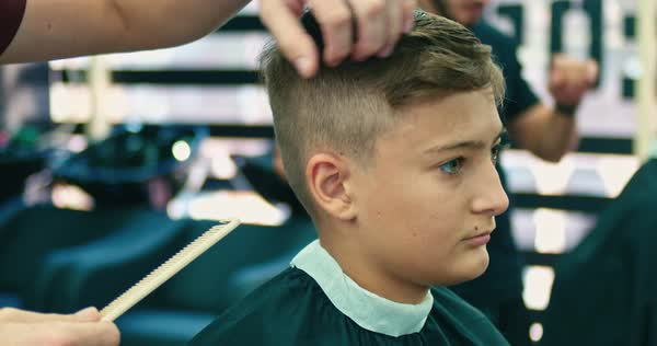 Serious Caucasian Boy Getting Hairstyle In Barbershop Stock Video