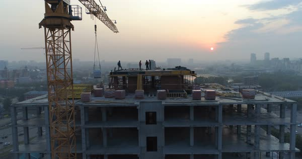 Silhouettes Of Builders On The Construction House In Evening Royalty Free
