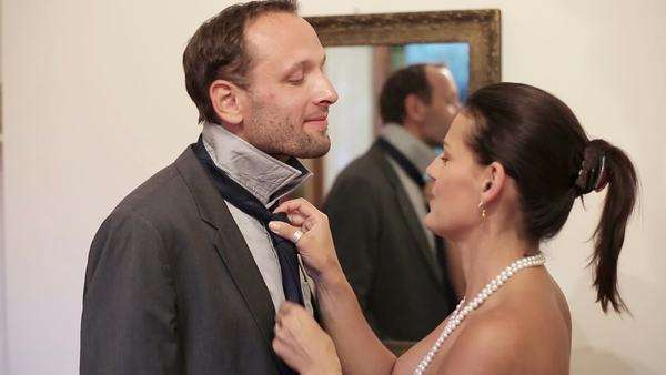 Wife knotting the necktie of her husband, helping and assisting him getting  dressed - Stock Video Footage - Dissolve