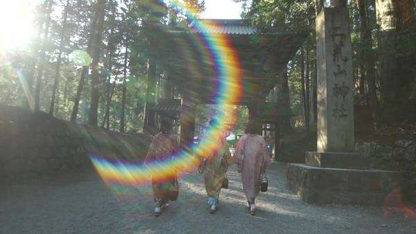 Three Japanese women dressed in kimonos walk below an arch. Royalty-free stock video
