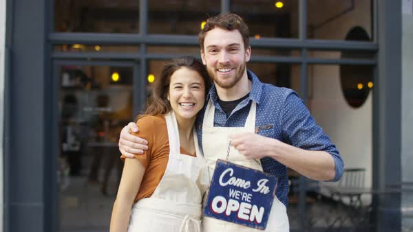 Happy owners outside cafe hold up a sign to show they are open for business. Royalty-free stock video