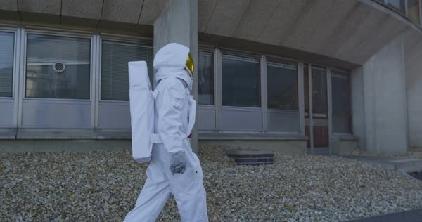 Astronaut looking for signs of life outside abandoned power station Royalty-free stock video