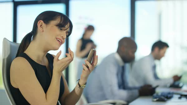 Bored woman checking her makeup with her phone with other bored colleagues in the background Royalty-free stock video