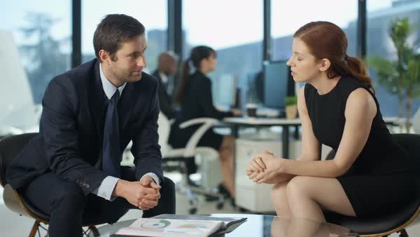Business man and woman in a meeting with colleagues working in background Royalty-free stock video