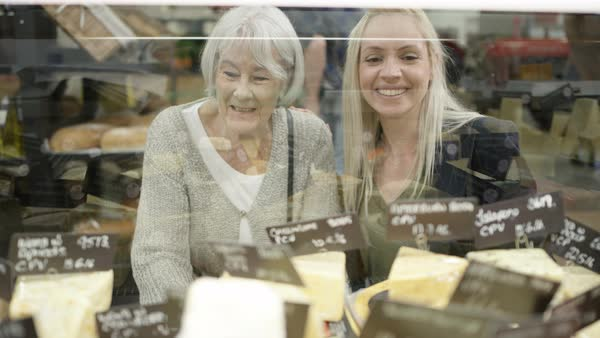Senior lady and adult granddaughter shopping at deli counter in supermarket Royalty-free stock video