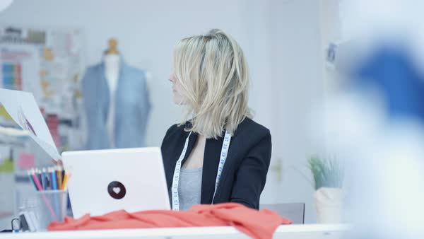 Portrait of smiling dressmaker working on laptop in her studio Royalty-free stock video