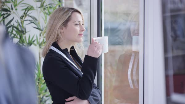 Fashion designer taking a break, drinking hot drink and looking out of window Royalty-free stock video