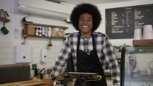 Portrait of friendly smiling worker standing behind counter in coffee shop Royalty-free stock video