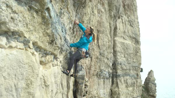 Young woman climbing vertical rock face trying to find a strong grip Royalty-free stock video