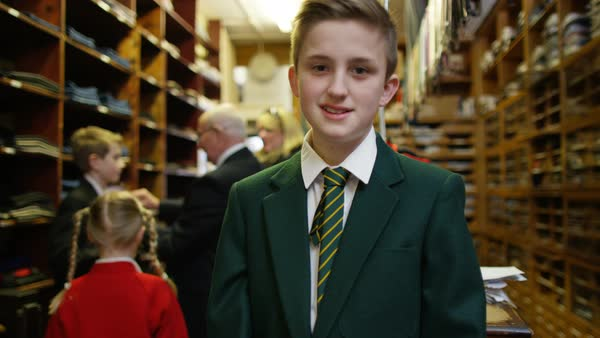 Portrait of smiling little boy trying on new school uniform in clothing store Royalty-free stock video