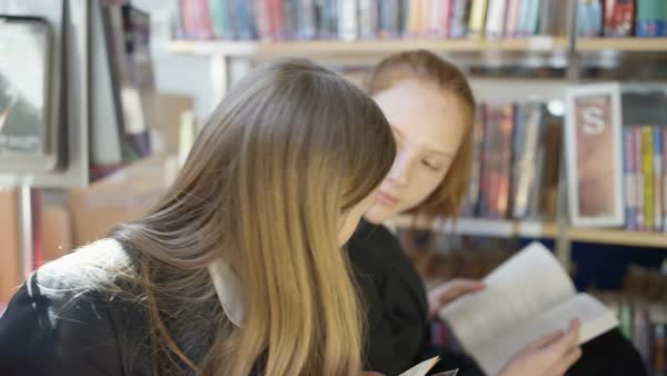 Young students reading books and chatting in school library Royalty-free stock video