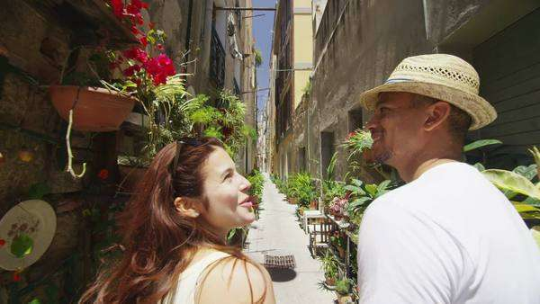 Attractive couple walking through narrow city alley with lots of plants Royalty-free stock video