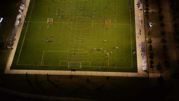 Aerial view of a floodlit soccer match at night in an American Stadium. Players paying ballgame on green pitch. Royalty-free stock video