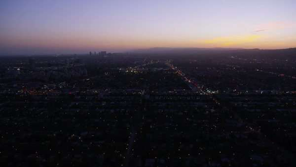 Aerial view of Los Angeles, California at night. Helicopter shot over homes and business buildings in American suburbs. Sunset or sunrise. Royalty-free stock video