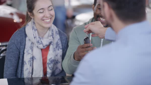 Happy couple with salesman signing contract & taking key to new car Royalty-free stock video