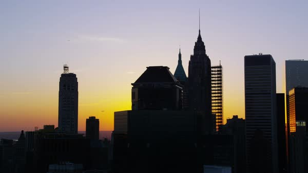 Aerial shot of sunset over New York City skyline. Silhouette cityscape skyscrapers and iconic landmarks. Sunrise golden glow over buildings, stores and Manhattan apartments. Royalty-free stock video