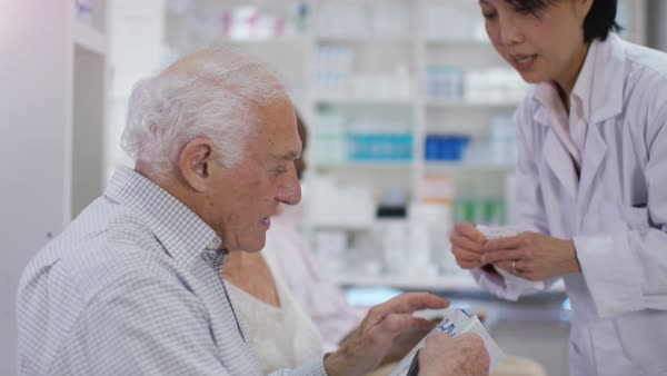 Friendly pharmacy worker gives prescription medication to customer Royalty-free stock video