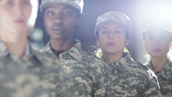 Close up on faces of female soldiers standing to attention and saluting. Royalty-free stock video