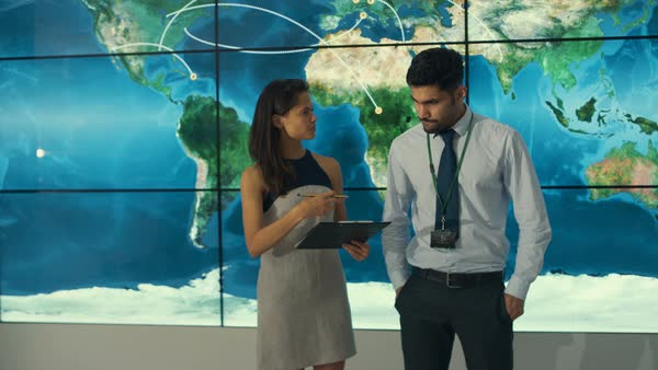 Businesswoman with tablet looking at large world map graphic on business team in control room with large world map graphic on video wall royalty sciox Images