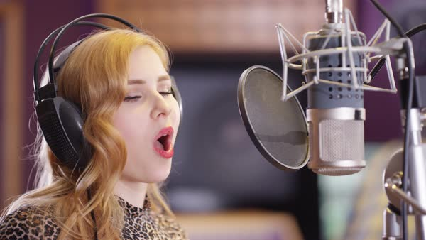 Portrait smiling female vocalist in recording studio singing into microphone. Royalty-free stock video