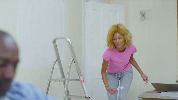 Couple in new home, man makes a phone call while his partner paints a wall. Royalty-free stock video