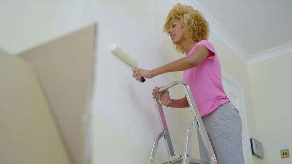 Attractive young woman on her own, painting a wall in new home. Royalty-free stock video