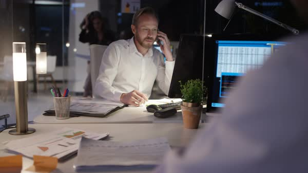 Cheerful businessman in the office at night, working on computer and talking on phone. Royalty-free stock video