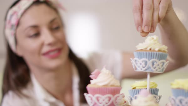 smiling woman with bakery business putting finishing touches onto cupcakes on a cake stand royalty