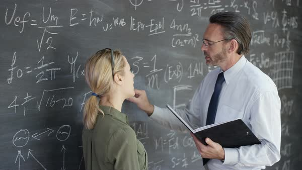 Academic man and woman writing math formulas on blackboard and discussing. Royalty-free stock video