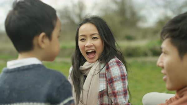 Happy young Asian family having a picnic outdoors in the countryside. Royalty-free stock video