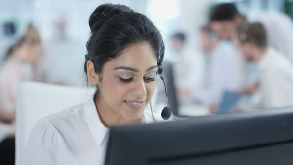 Friendly customer service adviser talking to a customer in busy call center. Royalty-free stock video