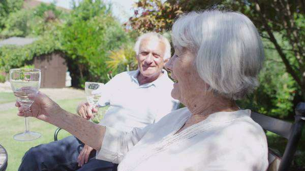 Cheerful senior couple relaxing in the garden at home Royalty-free stock video