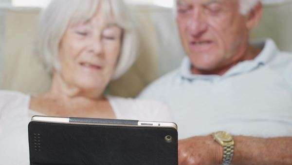 Cheerful senior couple relaxing at home with a computer tablet Royalty-free stock video