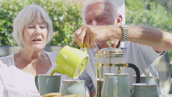 Affectionate senior couple relaxing and drinking coffee in conservatory on a sunny day Royalty-free stock video