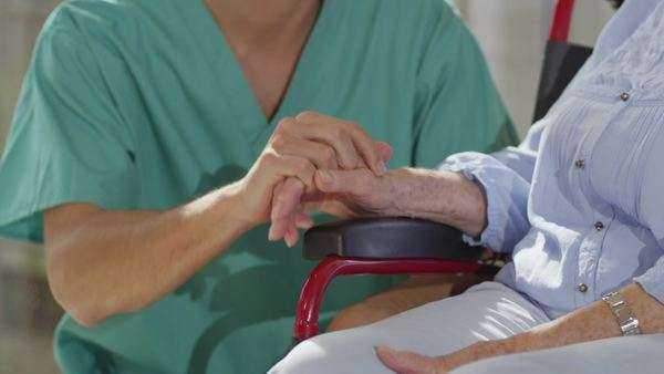 Caring male nurse giving support to elderly female patient in a hospital or residential care home Royalty-free stock video