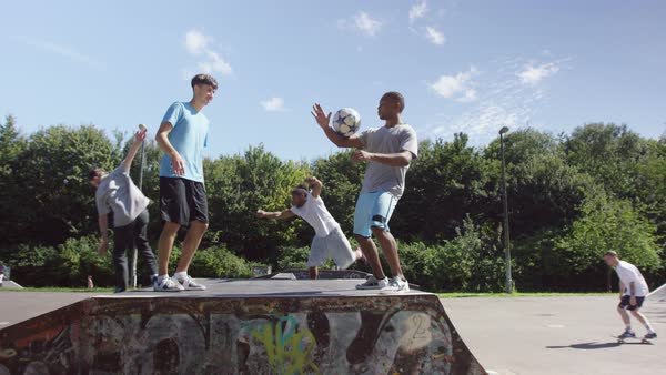 Young friends hanging out at skate park, practicing soccer skills and parkour jumps . Royalty-free stock video