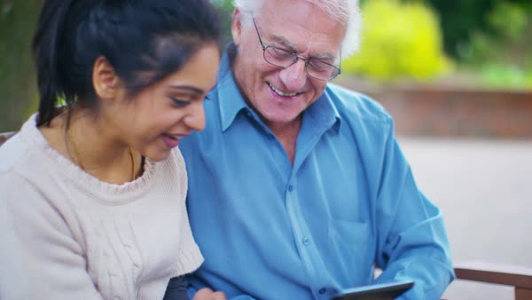 Caring young home support worker showing elderly gentleman how to use a computer tablet. Royalty-free stock video