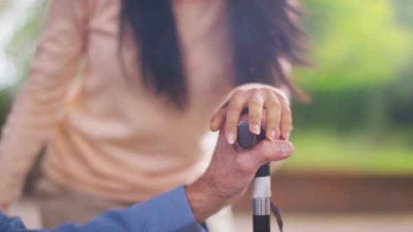 Caring young home support worker holding the hand of elderly gentleman with a walking stick. Royalty-free stock video