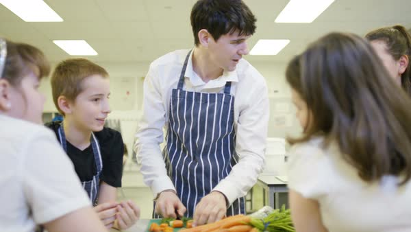 Teacher teaching pupils in school cookery class. Royalty-free stock video
