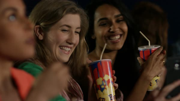 Happy young female friends in movie theatre pose to take a selfie before film starts. Royalty-free stock video
