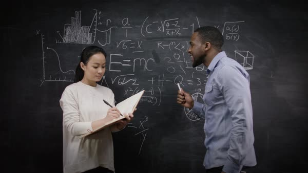 Academic man & woman writing math formulas on blackboard & discussing ideas - education & science concept. Royalty-free stock video